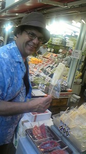 Dave-san enjoying a piece of a pinapple at a fruit store in front of  Yurakucho station