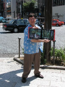 Dave-san  holding his first book of travel at the most expensive corner in Japan(the intersection of the 4th block in Ginza) (2010-8 photo by David Boyer)